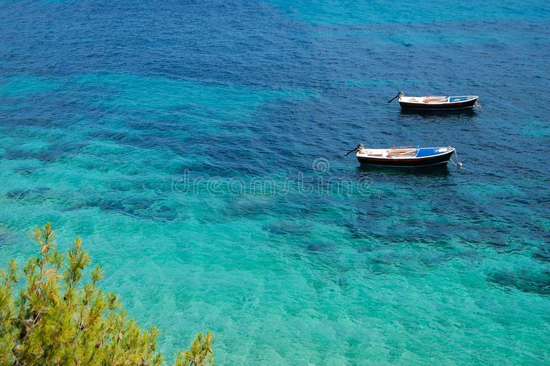 Two boats at rest in shallow water. Crystal clear turquoise waters of the Adriatic sea. Eastern bank of the famous Zlatni Rat Golden Horn beach in Bol on Brac stock photography