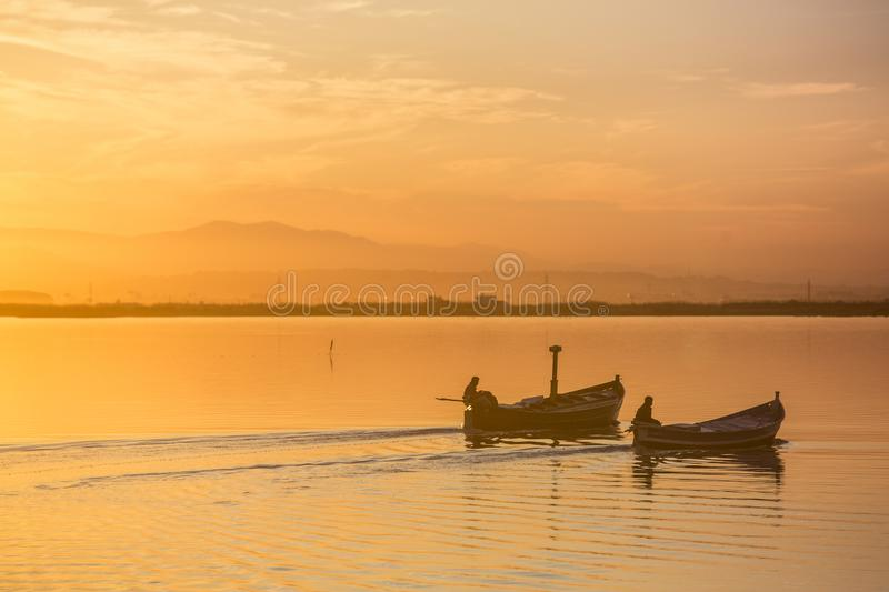 Two boats sailing through Albufera in Valencia at sunset royalty free stock photo
