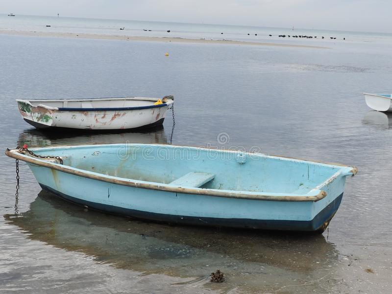 Two boats in shellow tide royalty free stock image