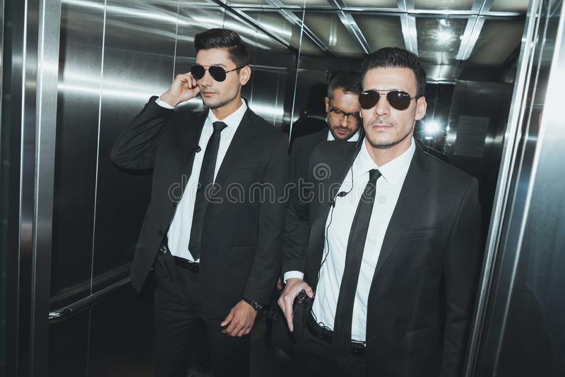 Two bodyguards and politician standing. In elevator royalty free stock photography