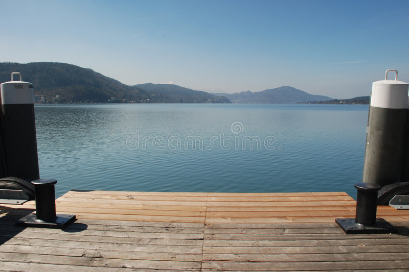 Two Bollards and the lake. Two Bollards on dock of the border of a lake in a sunny day with mountains and hills in the background - Austria royalty free stock images