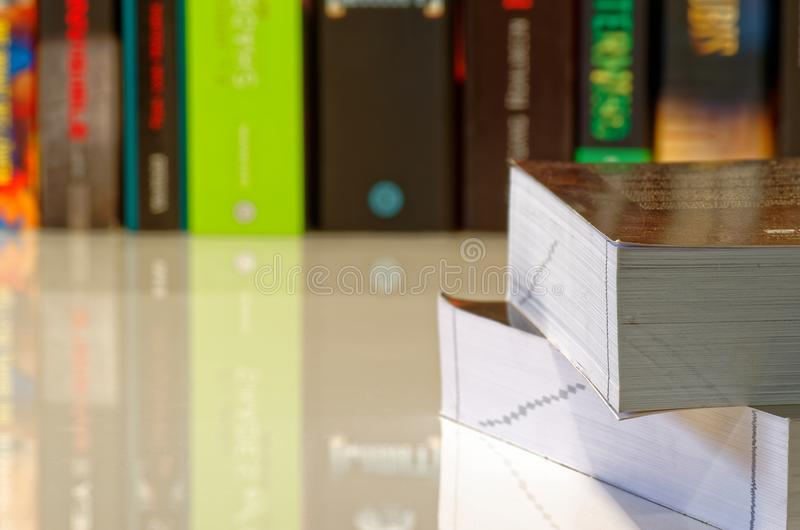 Two books on the table and a row of books in the background. Two books lying on a white table and colorful books in a row in background royalty free stock images