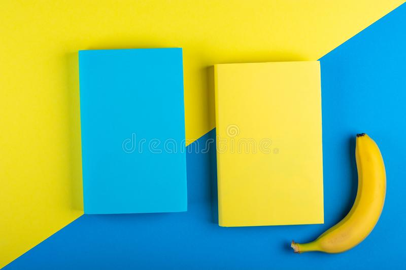 Two books Mock up and a banana on a yellow-blue background. stock photos