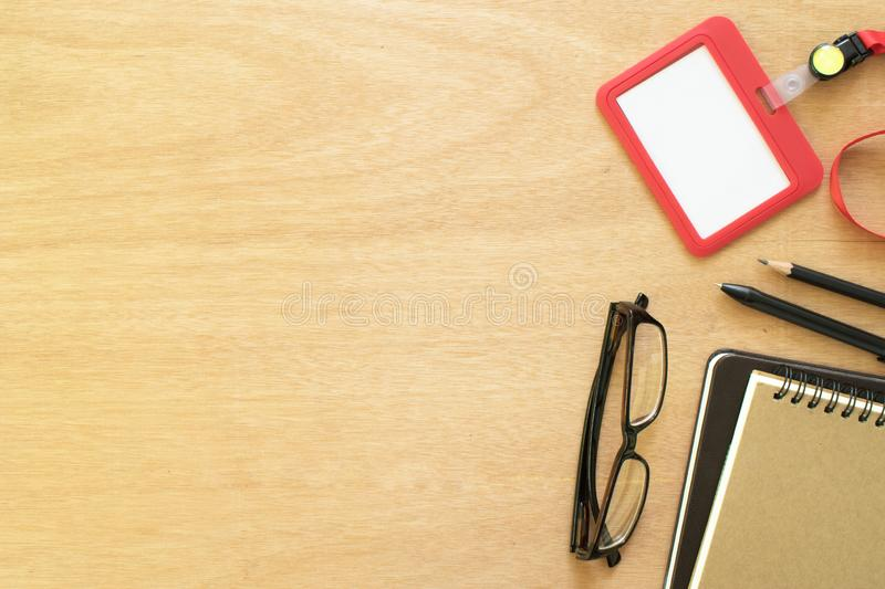 Two books, paperclip, pencil, pen, employee card, and eye glasses on rustic brown wooden desk. Lifestyle workspace, top view royalty free stock images