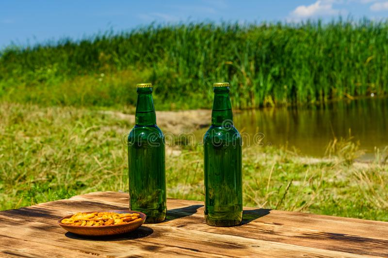 Two bottle of beer and ceramic plate with salted pretzels on woo royalty free stock images