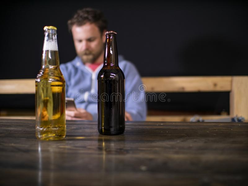 Two bottles of beer are standing on the table against the background of a sitting man who looks into the phone stock photos