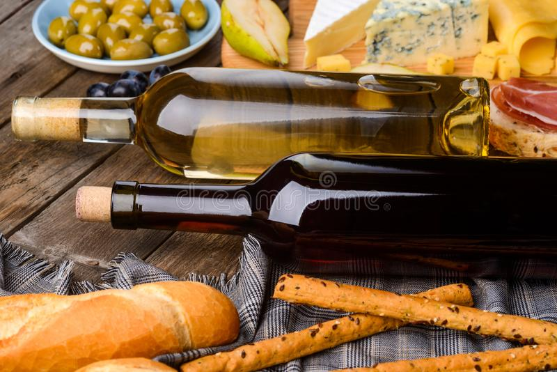 Two bottles and foods. Baguette and bread sticks on napkin, a plate of olives, a sprig of grape, pear halves, meat jerky and cheese on wooden table. Preparing stock photo
