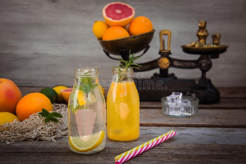 Two bottles with homemade lemonade and orange fresh juice with mint and ice on the rustic wooden background with fresh citrus in royalty free stock photos