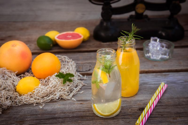 Two bottles with homemade lemonade and orange fresh juice with mint and ice on the rustic wooden background with fresh citrus in stock photo
