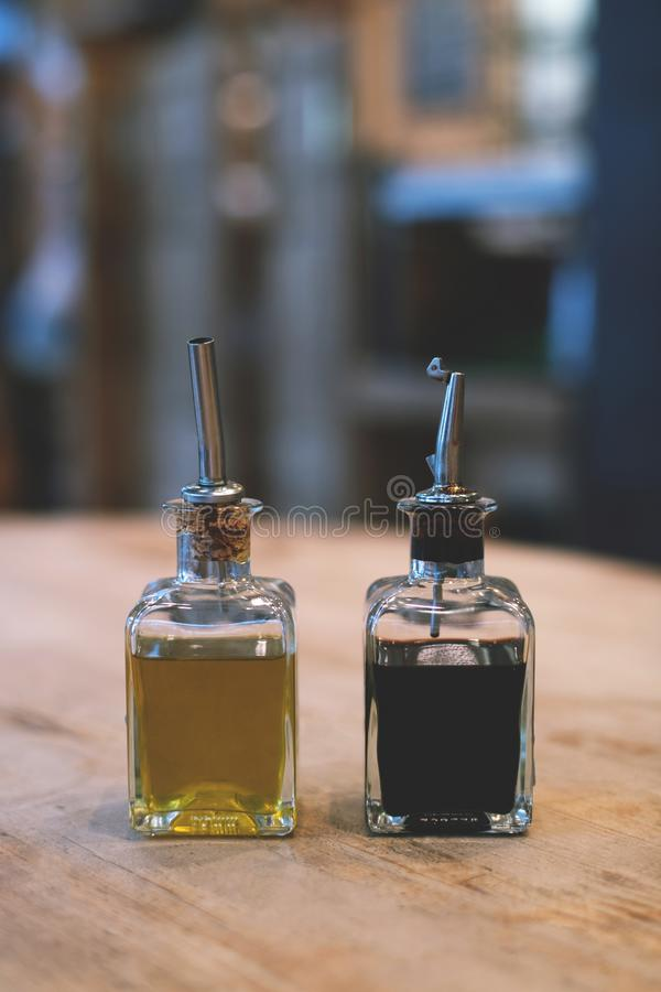 Two bottles of olive oil and of balsamico on the rustic table. stock images