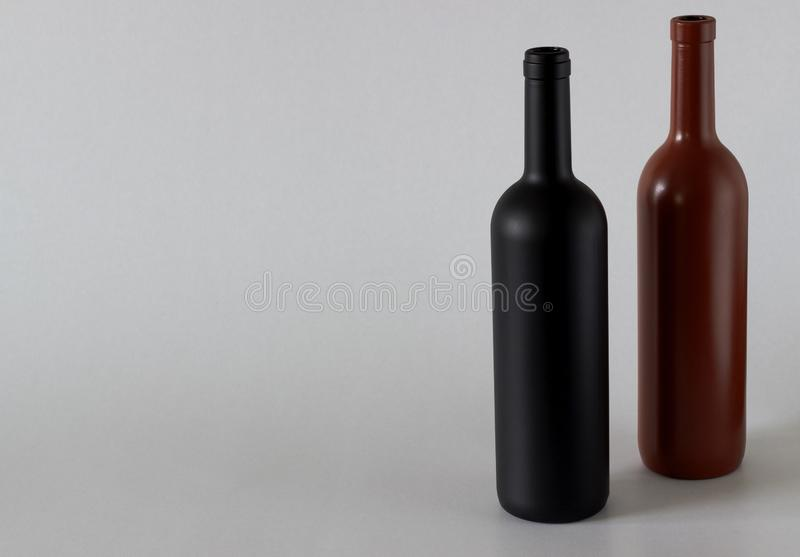 Two bottles of wine of black and red on a white background stock images