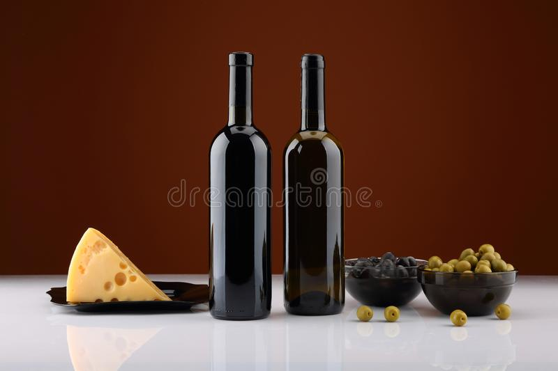 Two bottles of wine, olives and cheese royalty free stock photography