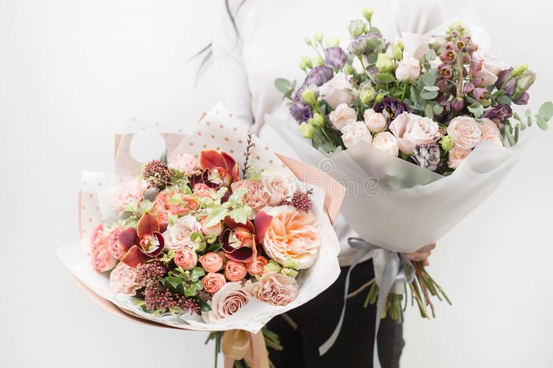 Two bouquet of beautiful flowers in women`s hands. Floristry concept. Spring colors. the work of the florist at a flower royalty free stock image