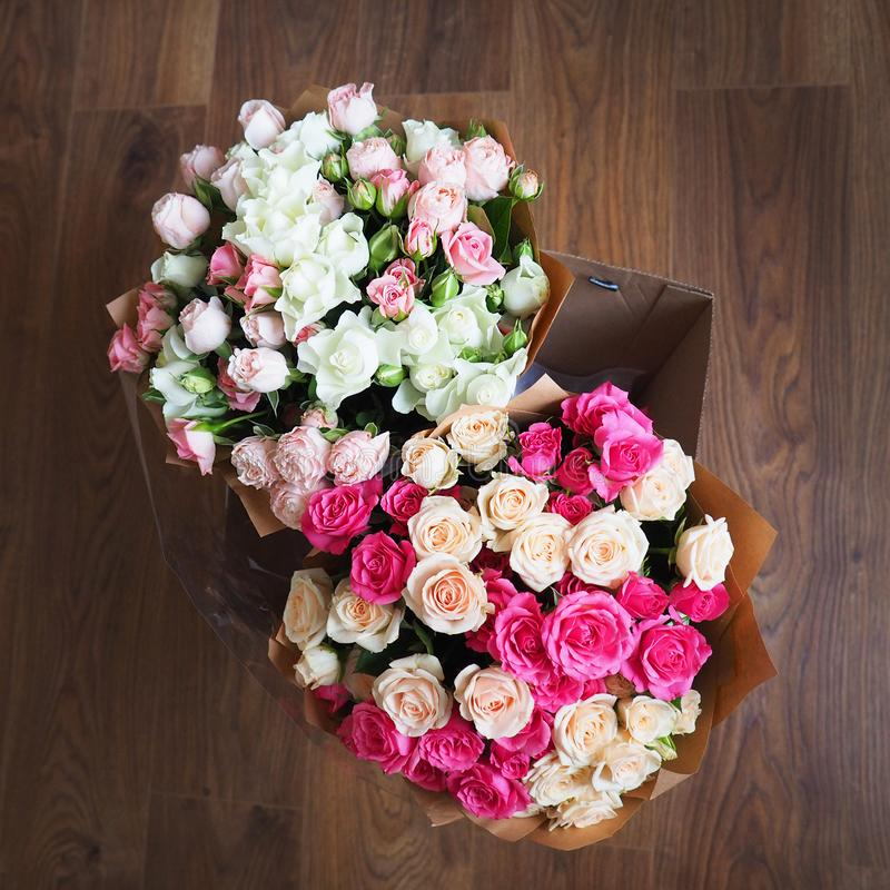 Two bouquets with roses of different colors in Kraft paper royalty free stock photo
