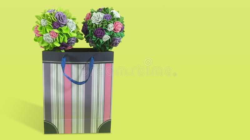 Two bouquets of roses with green leaves made of foamy inside a paper gift bag with purple stripes on green background stock photos