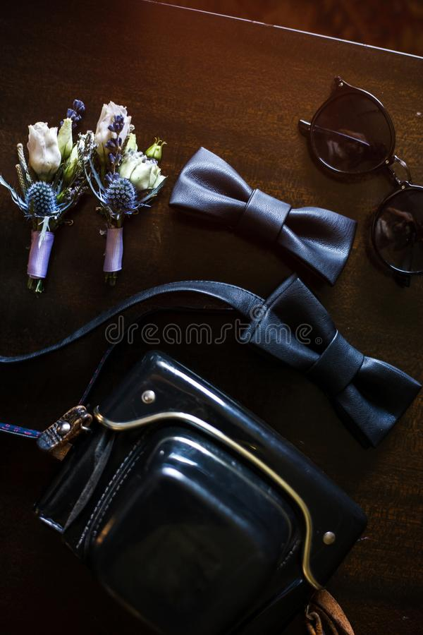 Two bow-ties and a bag are laying on the table. There are sunglasses and small flower bouquets near them stock image