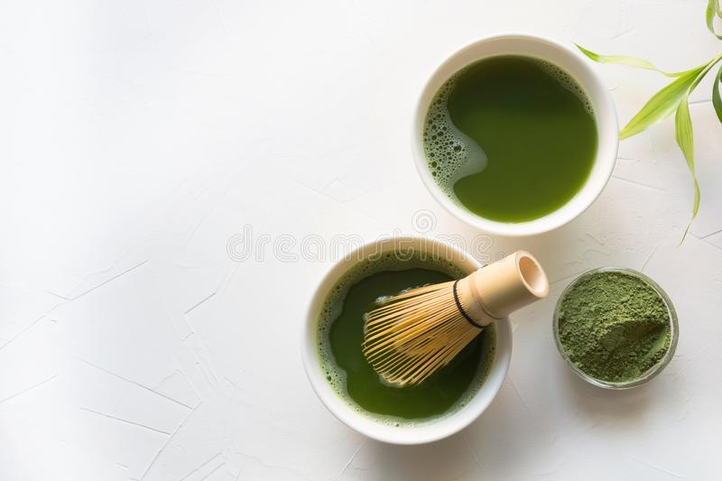 Two bowl green matcha tea and bamboo whisk on white concrete table. Top view royalty free stock photo