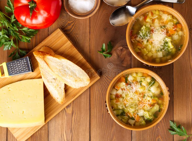 Two bowl of minestrone soup with cheese on cutting board and vegetables on rustic wooden background, top view. Two bowl of minestrone soup with cheese on a stock images