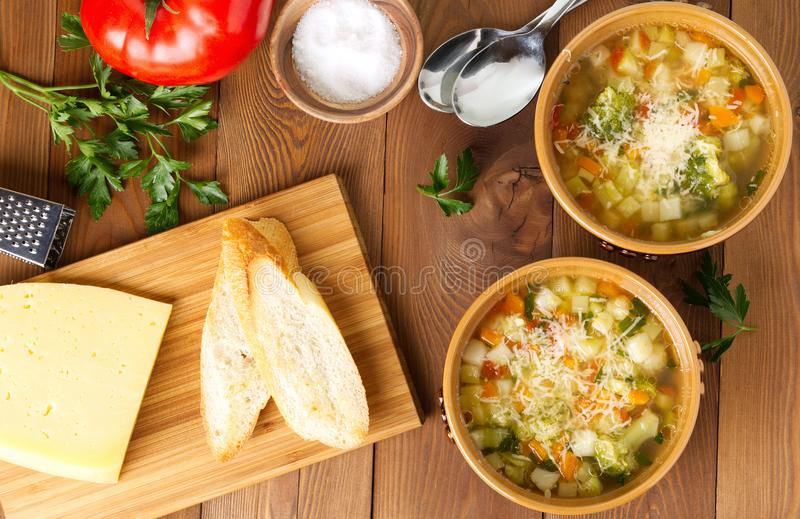 Two bowl of minestrone soup with cheese on cutting board, vegetables on rustic wooden background, top view, long width. Two bowl of minestrone soup with cheese royalty free stock photography