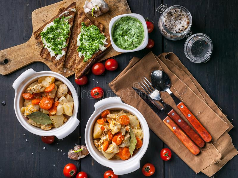 Two bowls of chicken baked with potatoes and carrots, sandwich with cheese and cherry tomatoes on a dark wooden background. Top stock photo