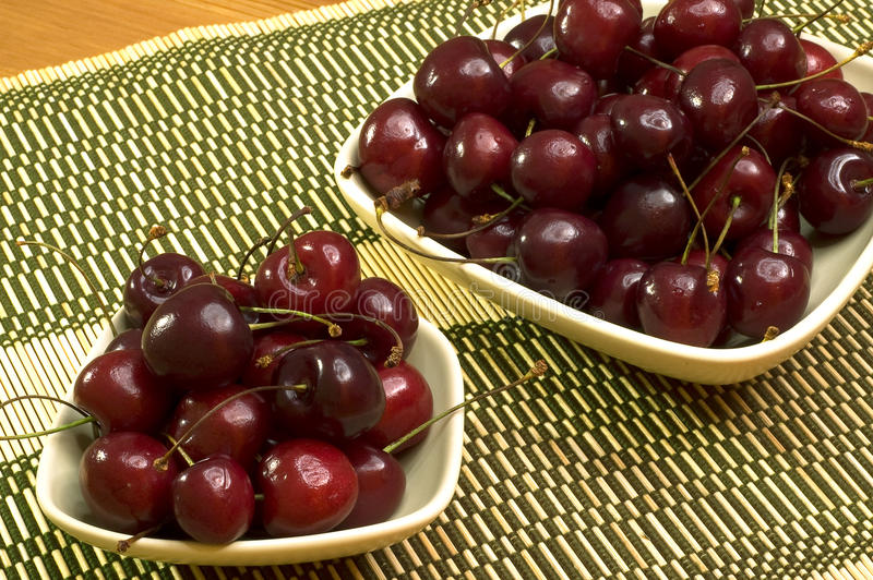 Two bowls with fresh cherries on a mat 1 stock photos