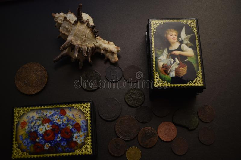 Two boxes with coins on a black background. royalty free stock image