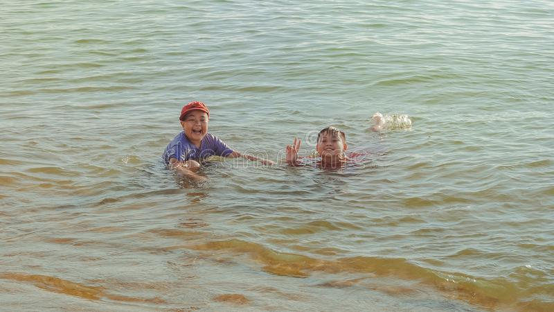 Two Boy on Brown Body of Water stock photography