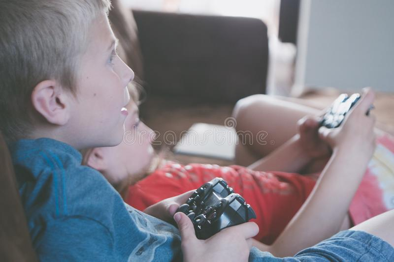 Two Boy and Girl Holding Game Controllers stock photography