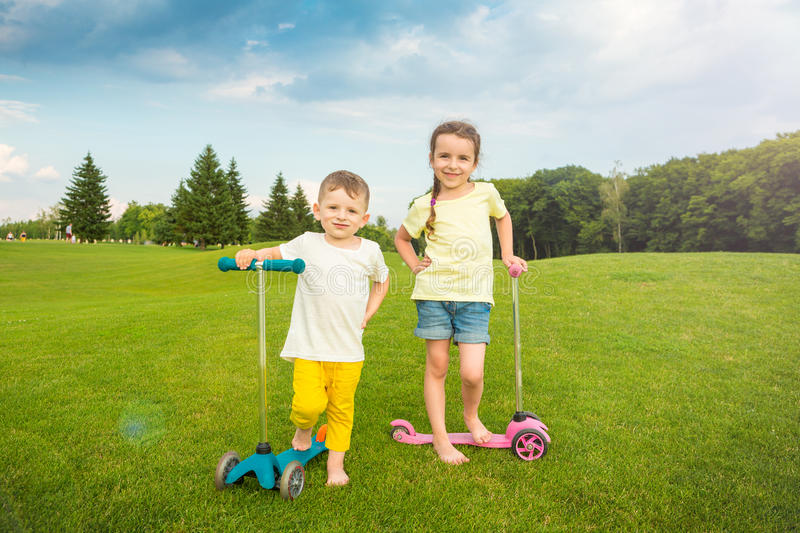 Two boy and a girl standing on the summer green field. stock photo