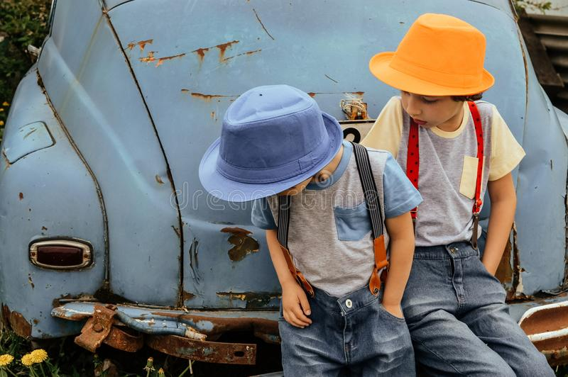 Two Boy in Grey Shirts and Blue Overall Pants Sitting on Blue Car Bumper royalty free stock photography