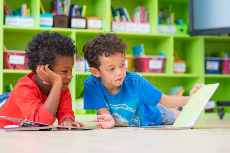Two boy kid lay down on floor and reading tale book in preschoo. L library,Kindergarten school education concept royalty free stock image