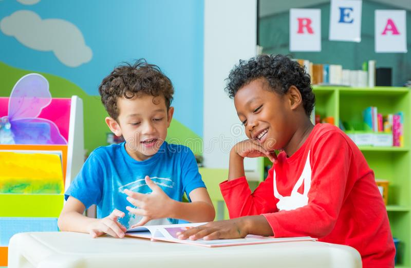 Two boy kid sit on table and reading tale book in preschool lib. Rary,Kindergarten school education concept royalty free stock photo