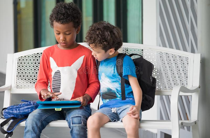 Two boy kid sitting on bench and playing game on tablet at preschoo,Kindergarten school education concept.diversity children. Two boy kid sitting on bench and stock images