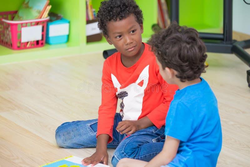 Two boy kid sitting on floor and taking in preschool library,Ki. Ndergarten school education concept.diversity children stock photography