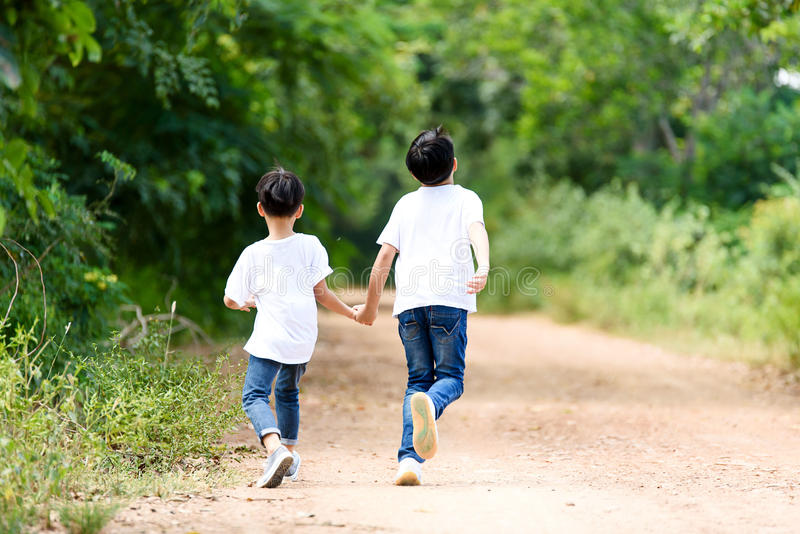 Two boy run in the park. Two young Thai boy run together on the crack road in the natural park stock image