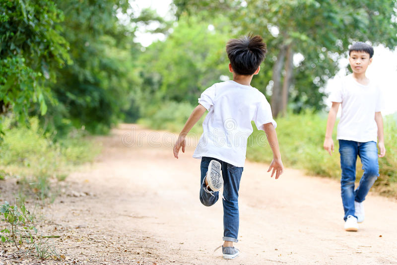 Two boy run in the park. Two young Thai boy run together on the crack road in the natural park royalty free stock photo