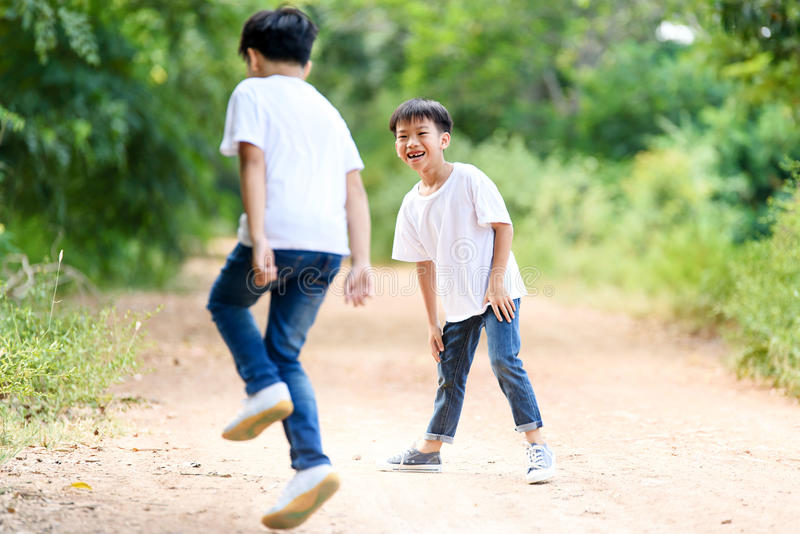 Two boy run in the park. Two young Thai boy run together on the crack road in the natural park stock images