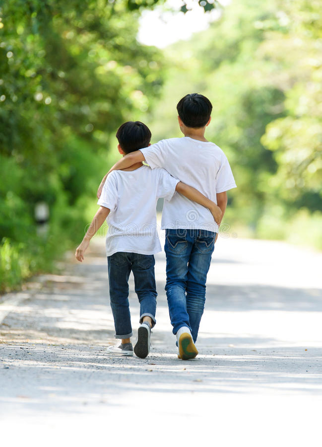 Two boy run in the park. Two young Thai boy run together on the crack road in the natural park royalty free stock photos