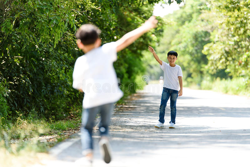 Two boy run in the park. Two young Thai boy walk and wave his hand in the park stock images
