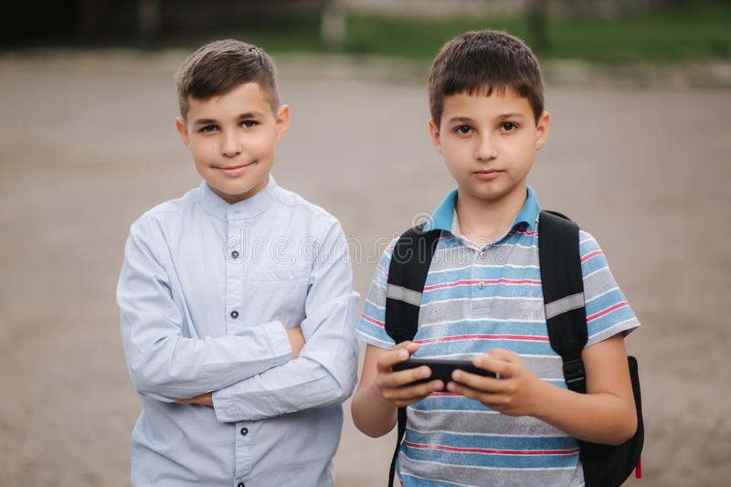 Two boy sitting on the bench and play online games. One boys with backpack. Young boys use their phones royalty free stock photography