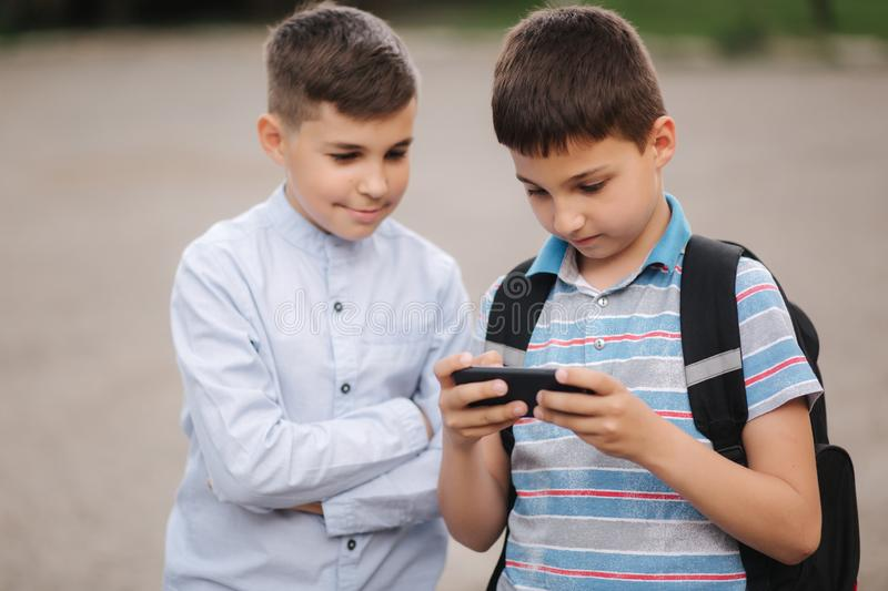 Two boy sitting on the bench and play online games. One boys with backpack. Young boys use their phones stock photos