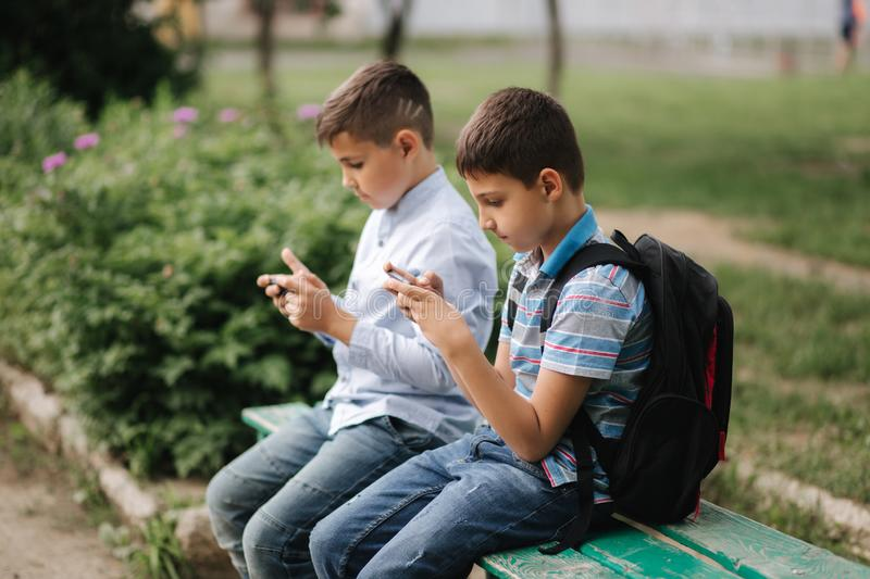 Two boy sitting on the bench and play online games. One boys with backpack. Young boys use their phones stock images