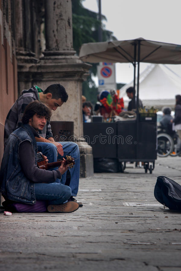 Two boy street performer playing and singing sitting on the ground stock photos