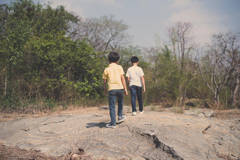 Two Boy walking on the rocky land. Vintage color, Two Boy walking through the rough rocky land in the day time with strong sunlight royalty free stock images