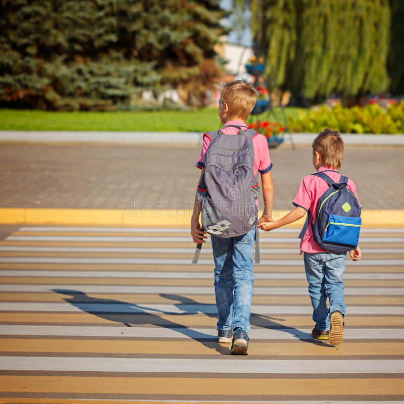 Two boys with backpack walking, holding on warm day on the road. Back view royalty free stock images