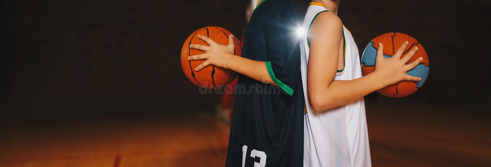 Two Boys Basketball Team Players Holding Basketballs on the Wooden Court. Basketball Training For Kids. Horizontal Background of Youth Basketball Players, Copy stock photo
