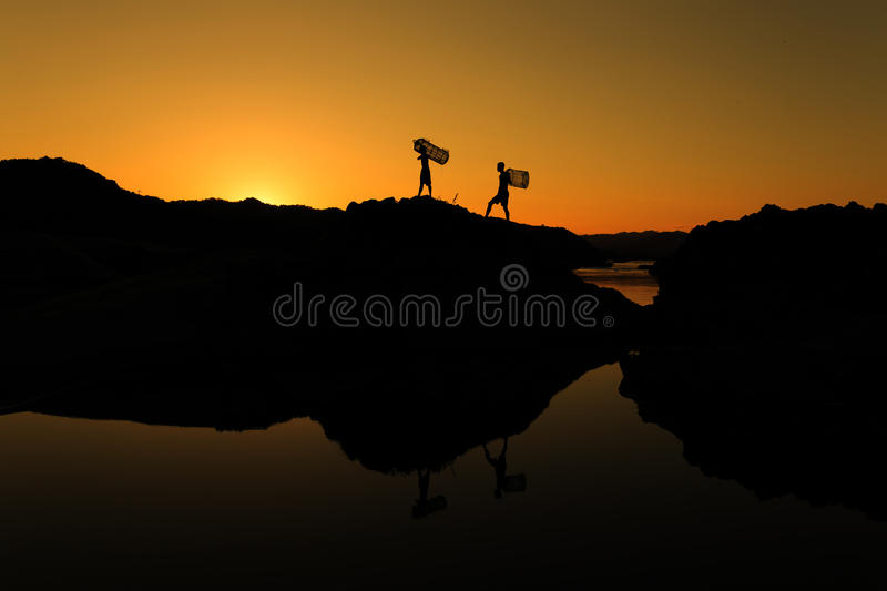 Two boys bearing the fishing gear. stock photography