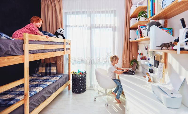 Two boys, brothers in kids room with bunk bed and wall shelves royalty free stock images