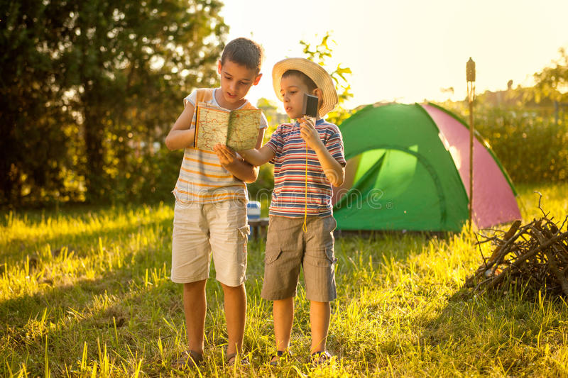 Two boys on a camping trip, learning how to read a compass. Camp in the tent - two brothers on the camping royalty free stock image