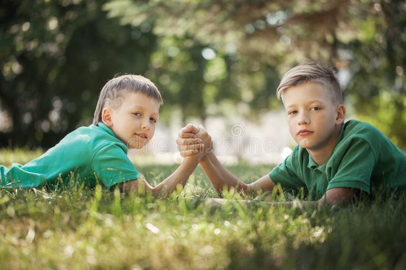 Two boys clasped hands engaged in an arm wrestle on green lawn in summer. Day royalty free stock photography